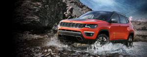 Orange Jeep Compass Driving Through River